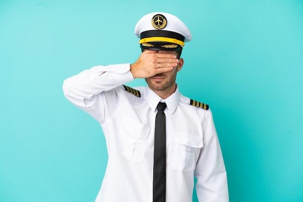 Piloto de avião caucasiano isolado em um fundo azul, cobrindo os olhos com as mãos. não quero ver nada
