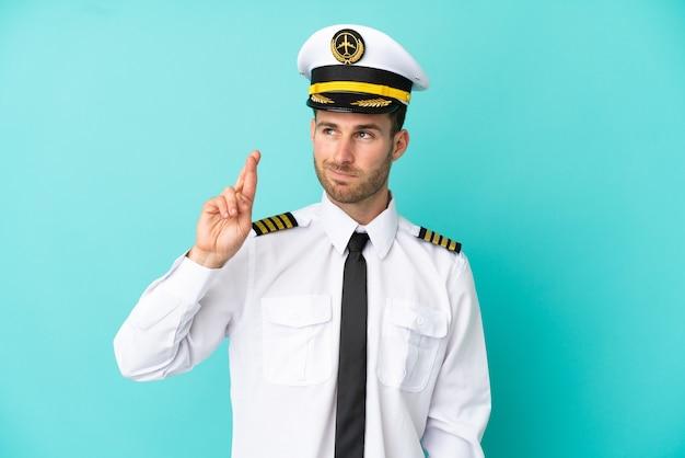 Piloto de avião caucasiano isolado em um fundo azul com os dedos se cruzando e desejando o melhor