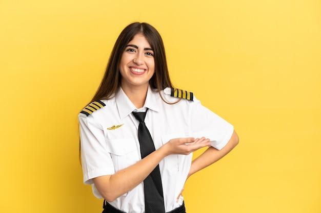 Piloto de avião isolado em fundo amarelo apresentando uma ideia enquanto olha sorrindo para