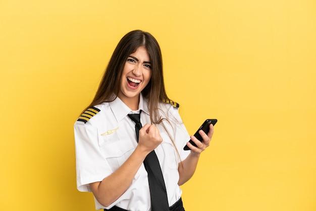 Piloto de avião isolado em fundo amarelo com o telefone na posição de vitória