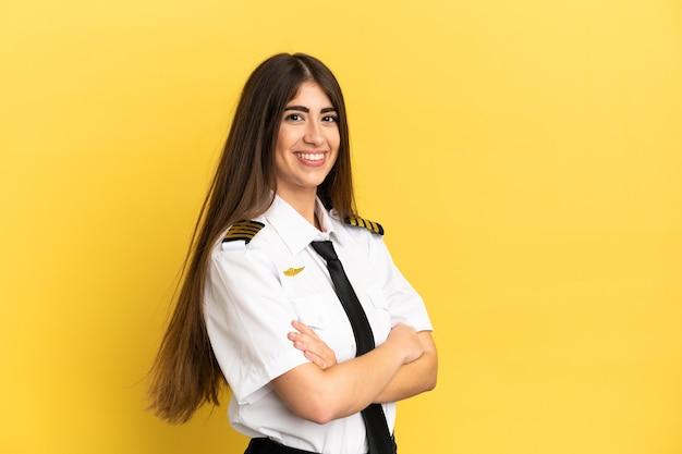 Piloto de avião isolado em fundo amarelo com os braços cruzados e olhando para a frente