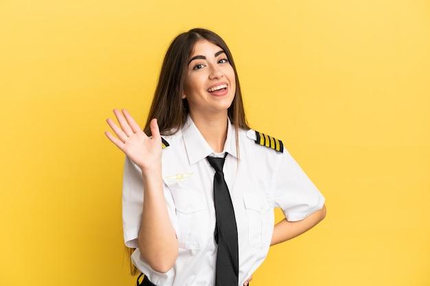 Piloto de avião isolado em fundo amarelo saudando com a mão com expressão feliz