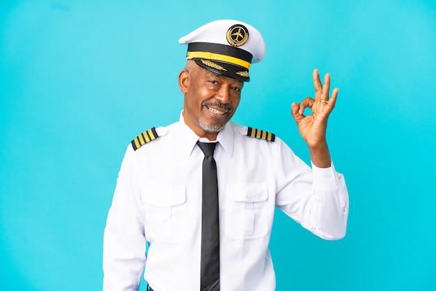 Piloto de avião sênior isolado em fundo azul, mostrando sinal de ok com os dedos