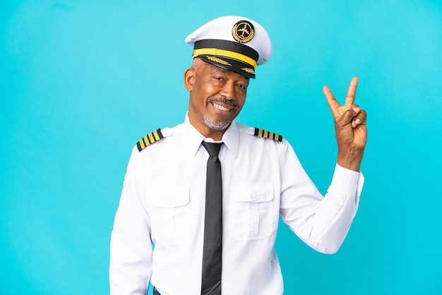 Piloto de avião sênior isolado em um fundo azul, sorrindo e mostrando sinal de vitória