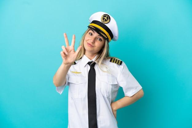 Piloto de avião sobre fundo azul isolado feliz e contando três com os dedos