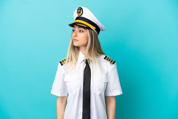 Piloto de avião sobre fundo azul isolado olhando para o lado