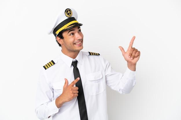 Piloto de avião sobre fundo branco isolado apontando com o dedo indicador uma ótima ideia