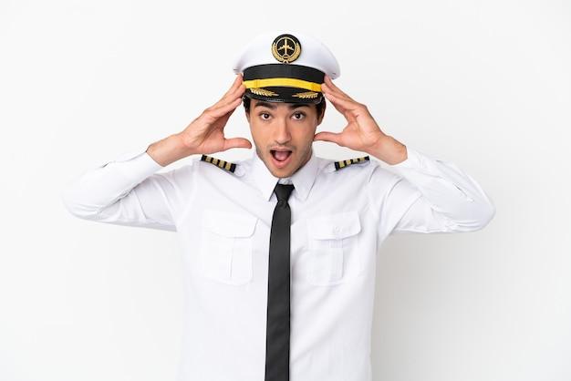 Piloto de avião sobre fundo branco isolado com expressão surpresa