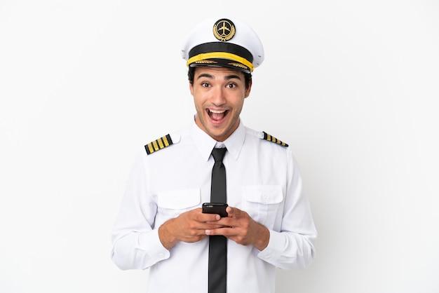 Piloto de avião sobre fundo branco isolado surpreso e enviando uma mensagem