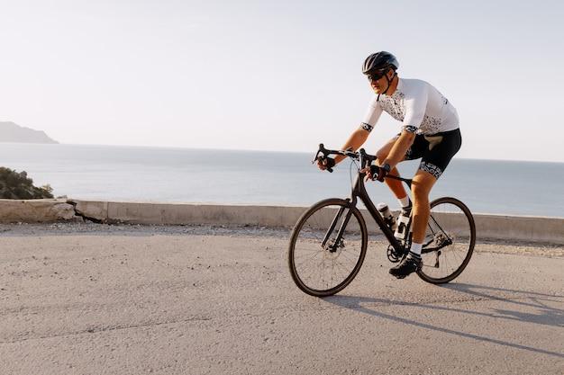 Piloto de bicicleta de estrada profissional em ação na estrada da montanha