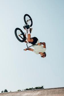 Piloto de bicicleta extrema realizando saltos perigosos