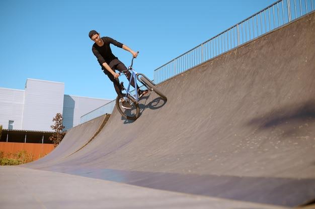 Piloto de bmx masculino fazendo truque na rampa, adolescente em treinamento no skatepark. esporte radical de bicicleta, exercícios de ciclismo perigosos, passeios de rua de risco, ciclismo no parque de verão