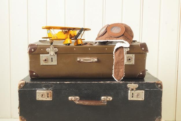 Piloto de capacete e brinquedo avião de metal amarelo duas velhas malas retrô madeira branca vintage tintom