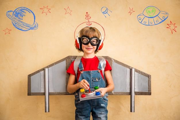 Piloto de criança brincando com jetpack de brinquedo em casa. sucesso e conceito de líder