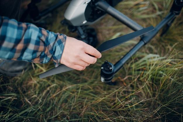 Piloto de homem verificando o drone quadricóptero antes do vôo aéreo e das filmagens.