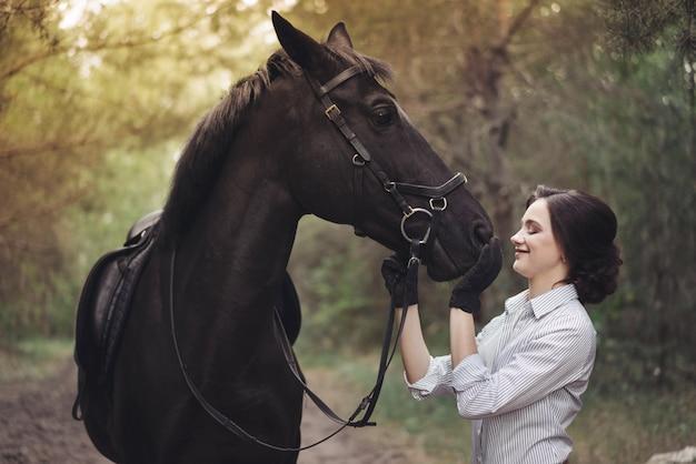Piloto de jóquei de menina bonita com um cavalo preto, vestido com uma camisa leve em um parque florestal verde.