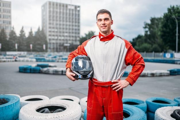 Piloto de kart com capacete nas mãos, pista de kart no fundo. kart