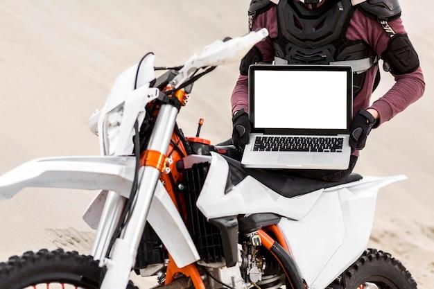 Piloto de moto elegante segurando laptop