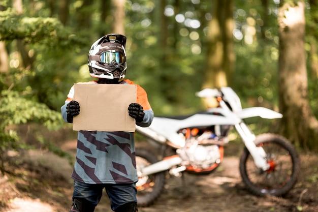 Piloto de moto elegante segurando placa de papelão