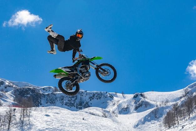 Piloto de moto em voo nas montanhas nevadas