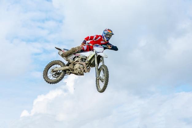 Piloto de moto em voo, pula e decola em um trampolim contra o céu.