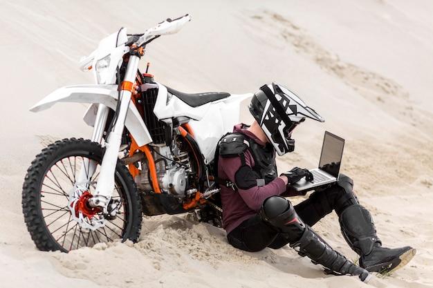 Piloto de moto navegando laptop no deserto