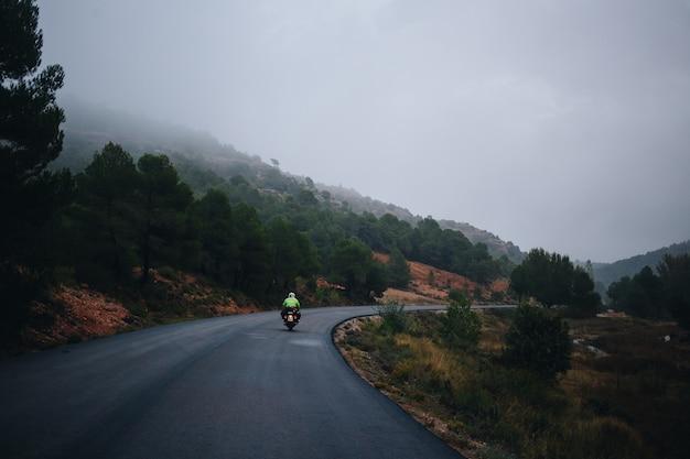 Piloto de motocicleta em estrada rural vazia