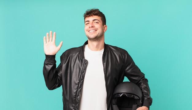Piloto de motocicleta sorrindo feliz e alegre, acenando com a mão, dando as boas-vindas e cumprimentando você ou dizendo adeus