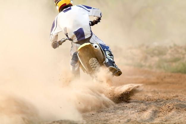 Piloto de motocross acelerando a velocidade na pista