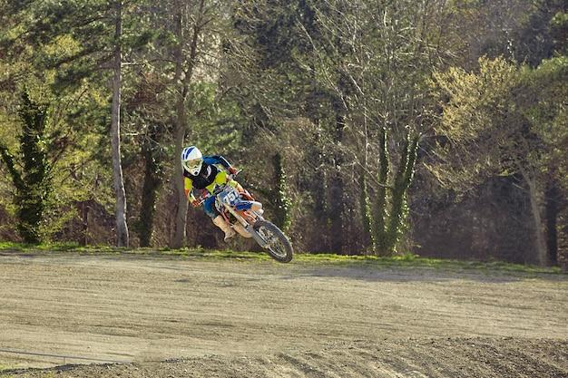 Piloto de motocross em ação acelerando a moto na pista de corrida
