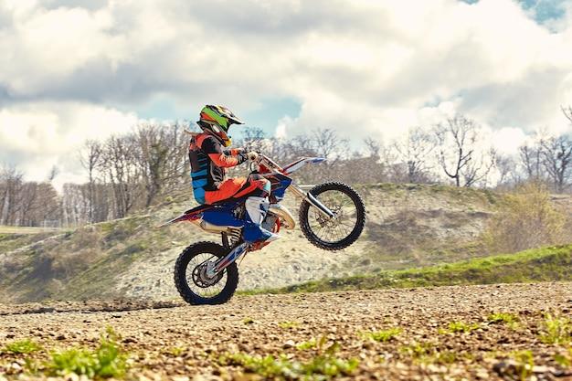 Piloto de motocross em ação acelerando a motocicleta decola e salta no trampolim na pista de corrida
