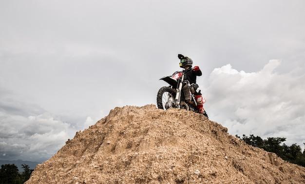 Piloto de motocross em sua bicicleta pronto para correr em pista de terra, esporte extremo e conceito de aventura de viagem.