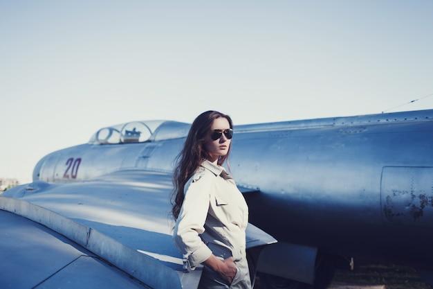 Piloto de mulher em óculos de sol perto do avião