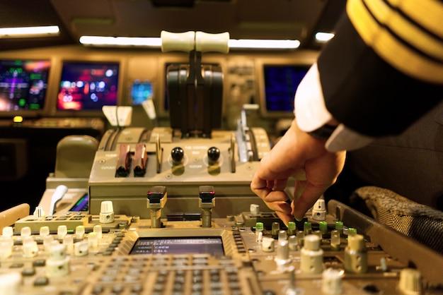 Piloto de uniforme no cockpit de avião está sintonizando o painel de rádio.
