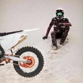 Piloto elegante com moto no deserto