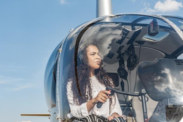 Piloto fêmea na cabina do piloto do helicóptero antes de descolar. jovem piloto de helicóptero.