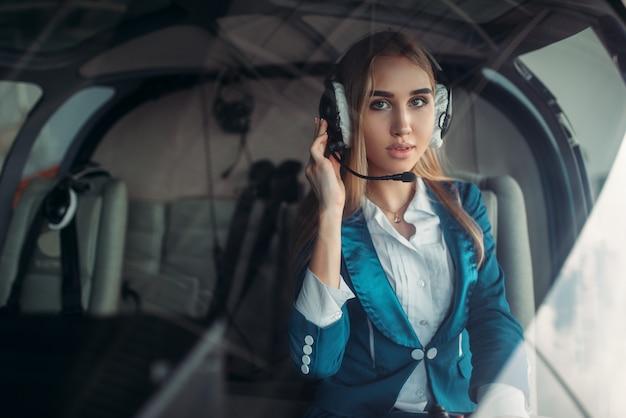 Piloto feminino em fones de ouvido na cabine do helicóptero