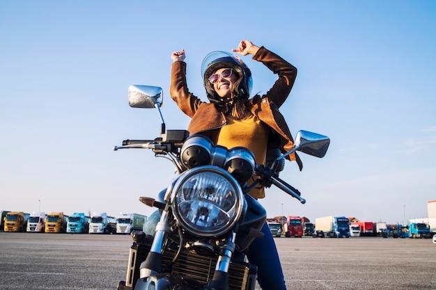 Piloto feminino sorridente sentado em sua motocicleta com os braços erguidos, mostrando felicidade