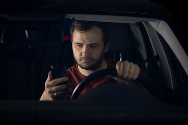 Piloto jovem sério confiante com barba por fazer se senta ao volante do carro à noite olhando para o smartphone