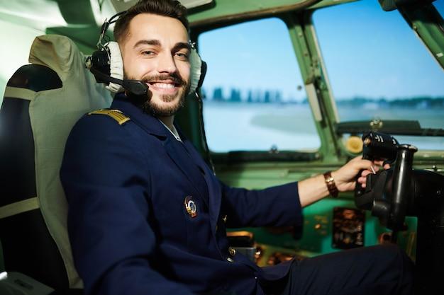 Piloto posando na cabine de avião