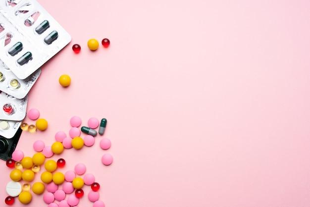 Pílula embalagem fundo rosa saúde farmacêutica medicamentos multicoloridos. foto de alta qualidade