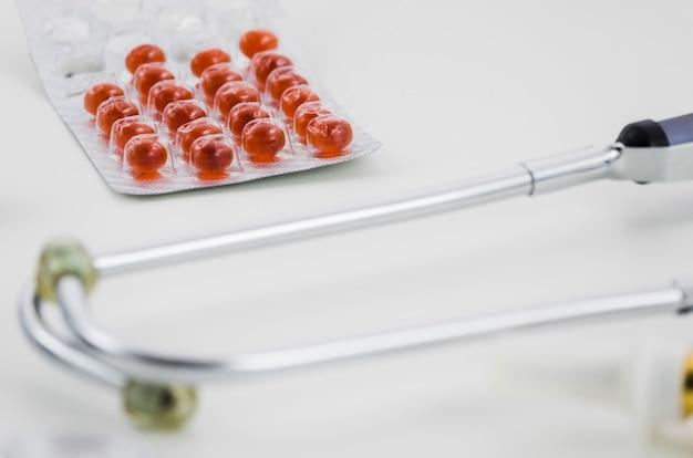 Pílula vermelha blister pack com estetoscópio no fundo branco