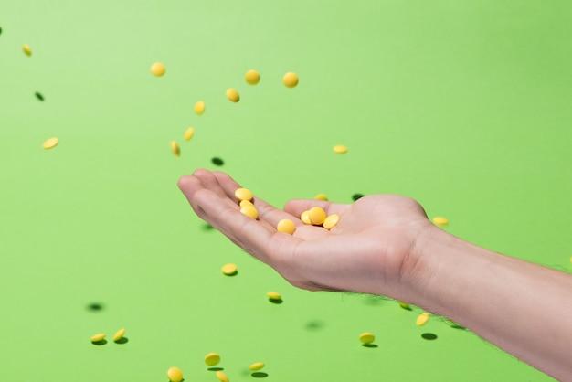 Pílulas amarelas voando na frente de um fundo verde