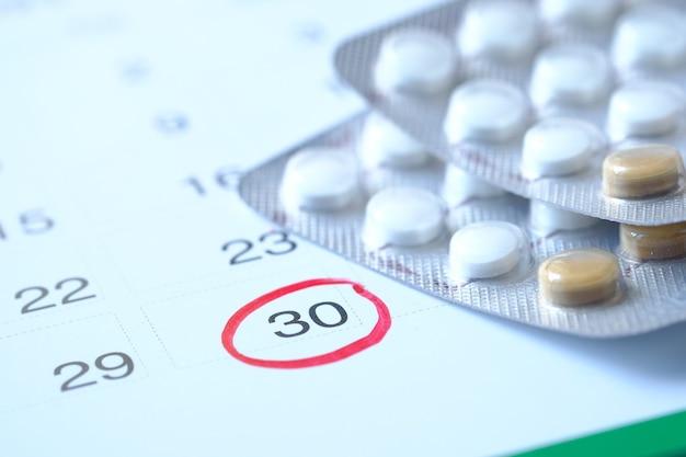 Pílulas anticoncepcionais e calendário na superfície de madeira, close-up