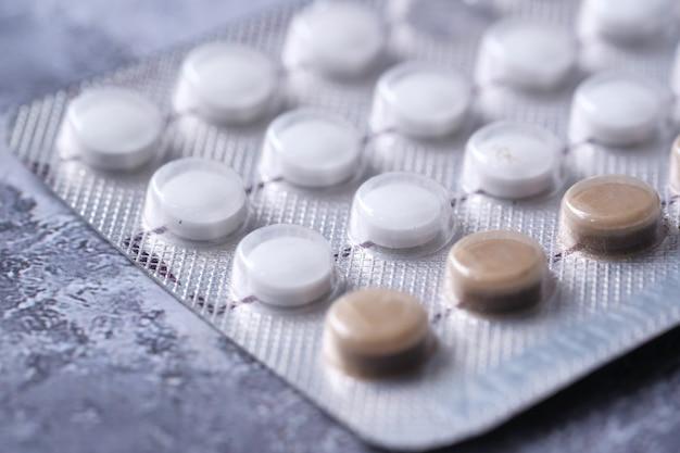 Pílulas anticoncepcionais em espaço negro, close-up