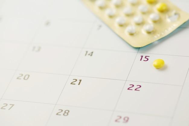 Pílulas anticoncepcionais na data do calendário. cuidados de saúde e medicina conceito de controle de natalidade.