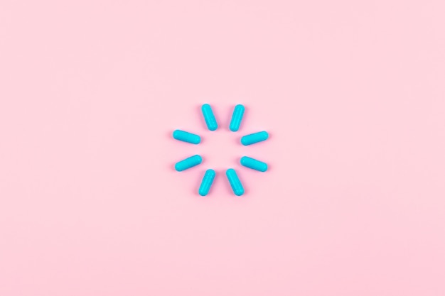 Pílulas azuis brilhantes no símbolo de carga no fundo rosa