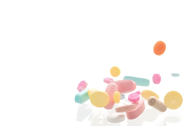 Pílulas coloridas de várias formas em fundo branco