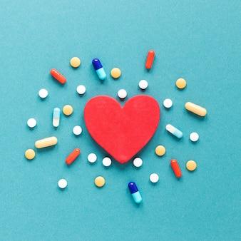 Pílulas coloridas de vista superior com coração em cima da mesa
