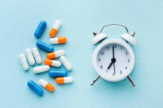 Pílulas coloridas de vista superior e relógio branco